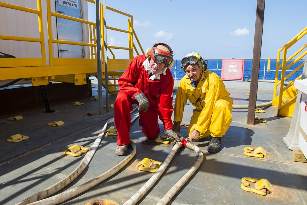 Civil service mariners Walter Ott, left, and William Lima, an able-bodied seaman and boatswain, respectively, with the container ship MV Cape Ray (T-AKR 9679), check a fire hose aboard the ship in the Mediterranean Sea July 17, 2014, in preparation for helicopter operations. The U.S. government-owned MV Cape Ray was modified and deployed to the eastern Mediterranean Sea to dispose of Syrian chemical agents in accordance with terms Syria agreed to in late 2013. (U.S. Navy photo by Mass Communication Specialist Seaman Desmond Parks/Released)